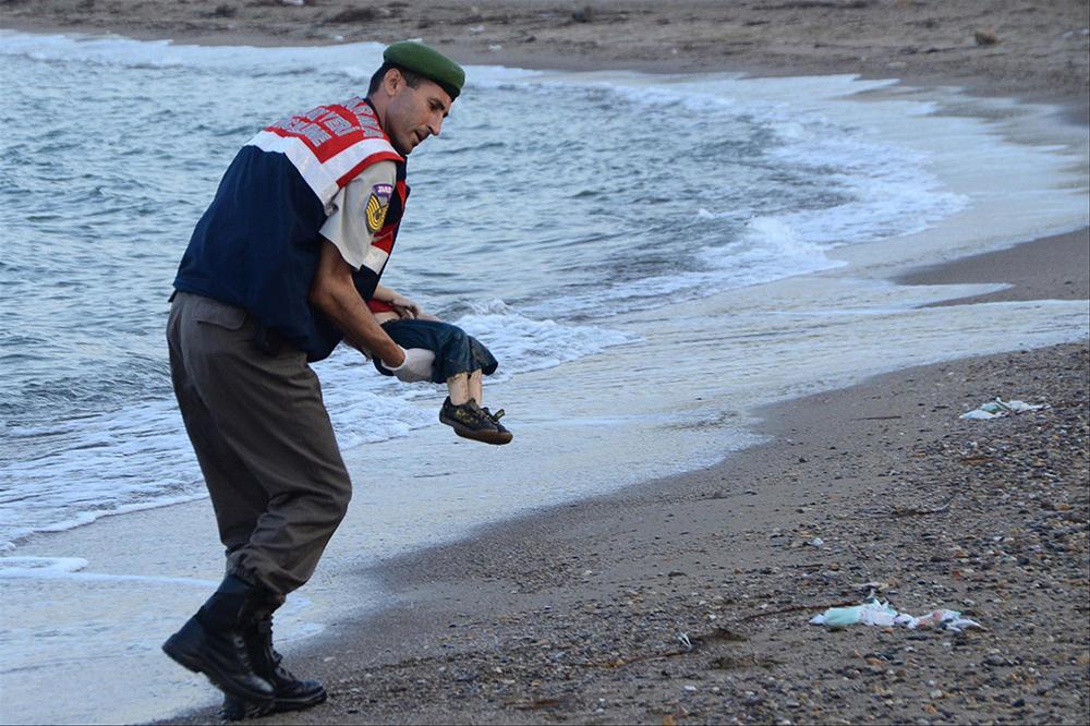 Um policial turco carrega o cadáver de uma criança migrante (Aylan Shenu) na costa de Bodrum, no sul da Turquia, em 2 de setembro de 2015, depois que um barco que transportava refugiados afundou ao chegar à ilha grega de Kos