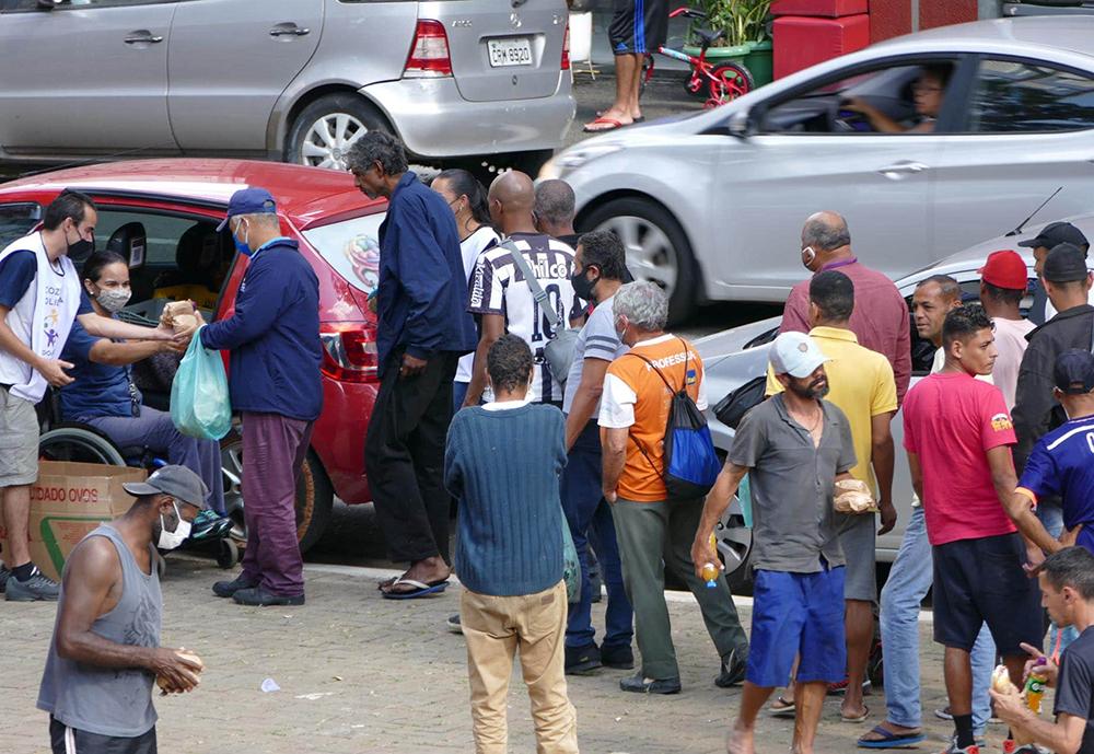 Pessoas em situação de rua fazem fila para receber alimentos na hora do almoço da ONG Cozinha Solidária na praça Marechal Deodoro, centro de São Paulo, no dia 2 de maio