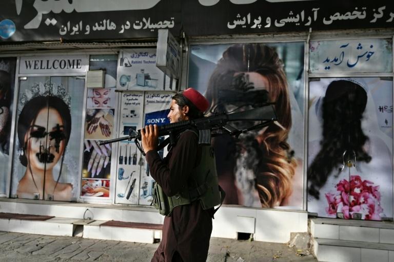 Talibã passa por vitrine pichada de salão de beleza feminino de Cabul, em 18 ago. 2021
