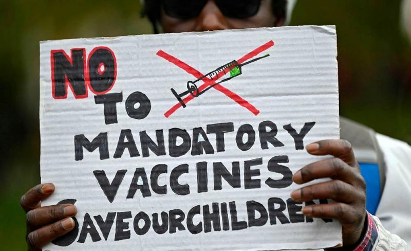Manifestante exibe cartaz contra obrigatoriedade da vacinação contra Covid, em Londres