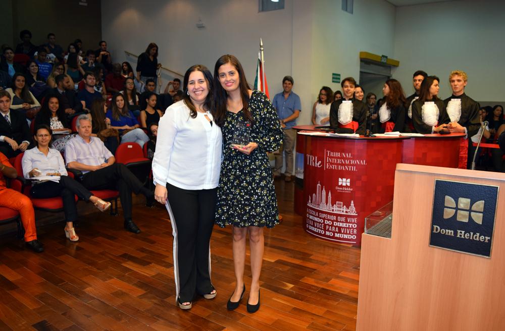 Professora Camila Martins entrega homenagem à aluna Aline dos Santos Lima, da Dom Helder.