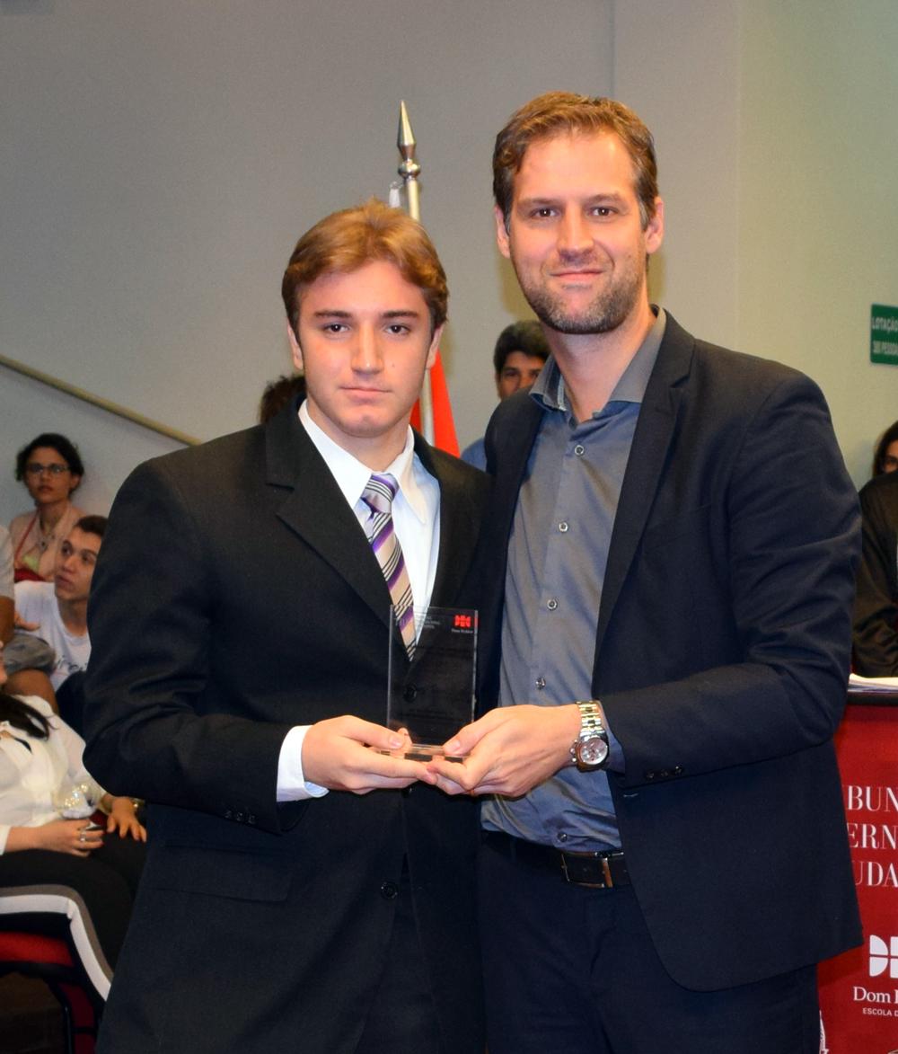 Professor Renato Campos entrega homenagem ao estudante Davi Jorge Vanni Saliba, do Colégio Santo Agostinho.