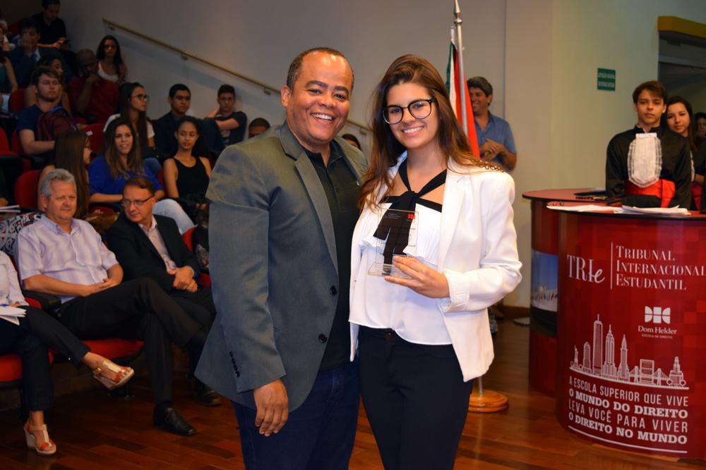 Professor Rogério Vieira entrega homenagem à aluna Giovanna Motta Miranda, do Colégio Marista.