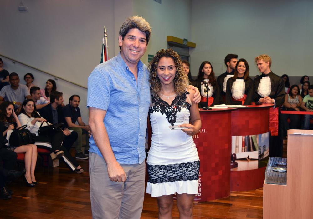 Professor Edmilson Ferreira entrega homenagem à estudante Luziana Marinho Fonseca Evangelista, da Dom Helder.
