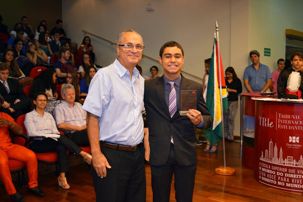 Professor Estevão Freitas entrega homenagem ao aluno Rafael Mansur Duarte, do Colégio Militar.
