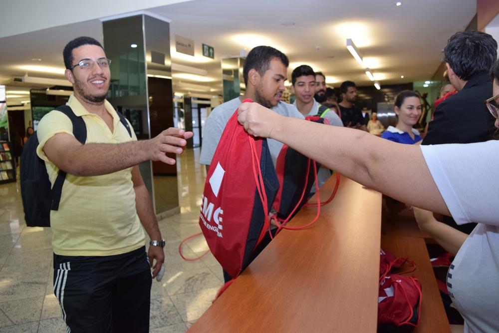 Alunos recebem um kit antes de entrar no auditório para a atividade.