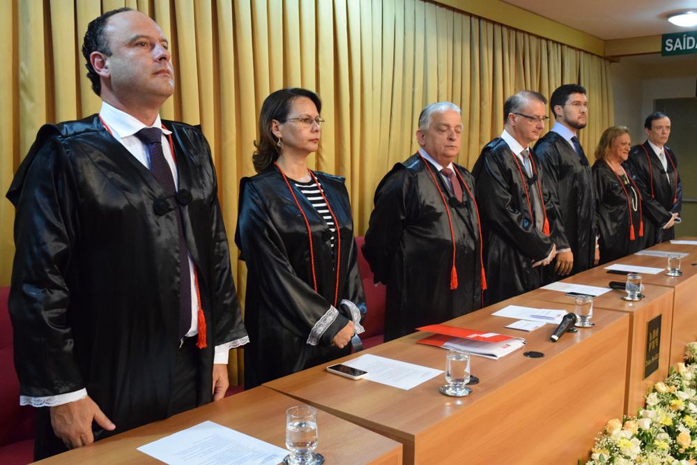 Membros que compõe a mesa solene se põem de pé para a execução do Hino Nacional.