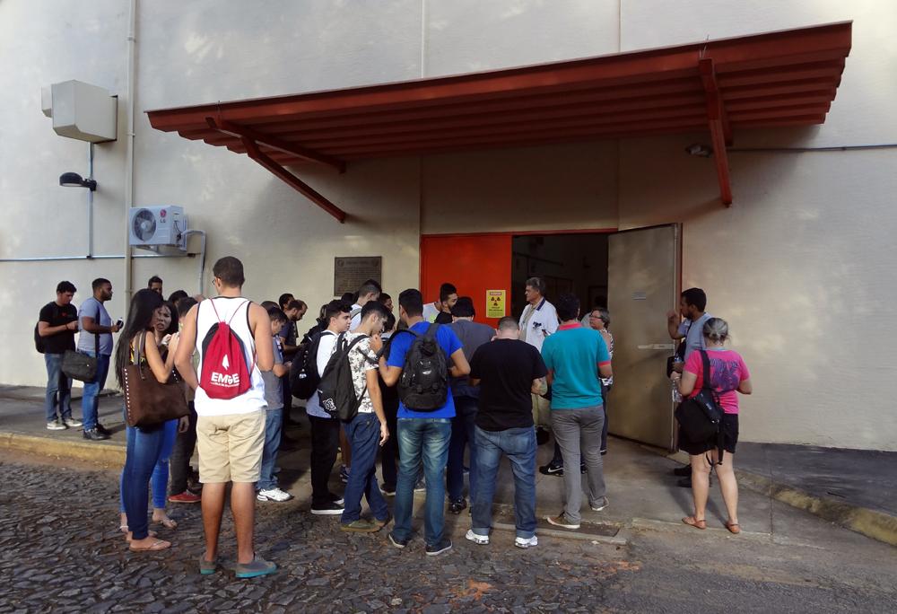 O operador Fausto Maretti Júnior recebe es estudantes na entrada do galpão que abriga o Triga IPR-R1.