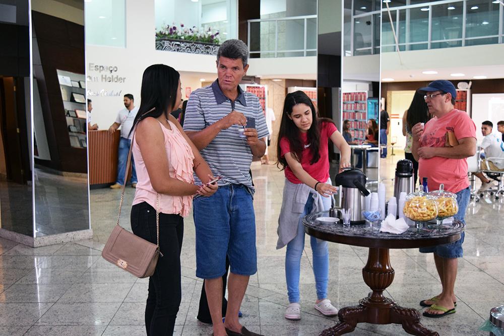 Pais e amigos aguardam vestibulando tomando um café na instituição.