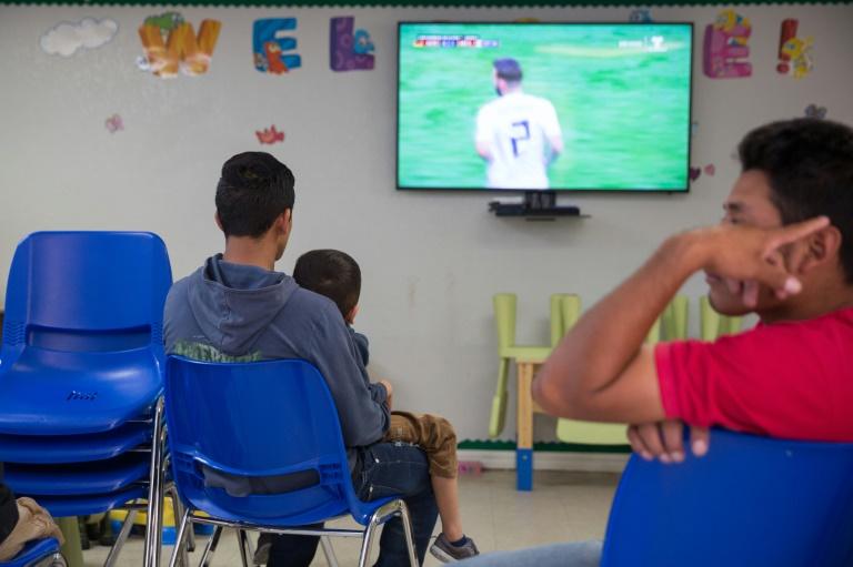 Pai e filho assistem a jogo da Copa em um centro de caridade católico no Texas, após solicitarem asilo nos Estados Unidos.
