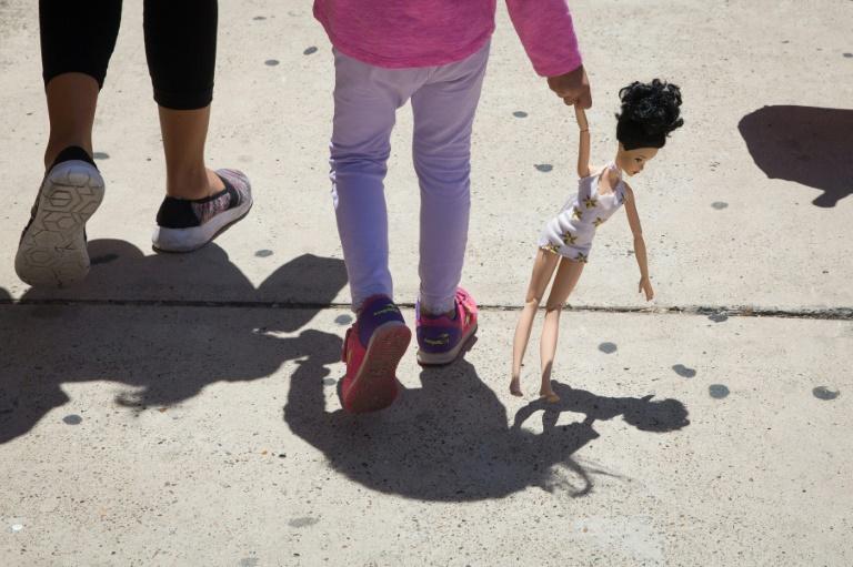Menina hondurenha carrega boneca ao lado de sua mãe em McAllen, Texas, depois de serem liberadas