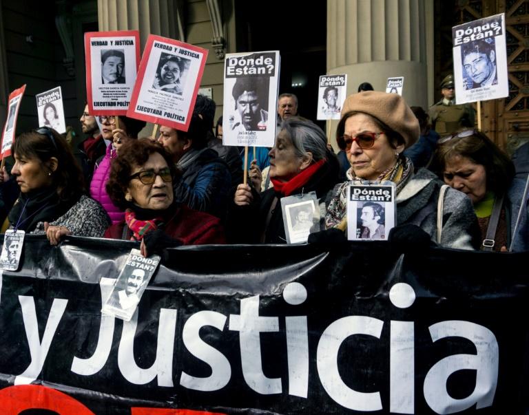 Portando fotos de pessoas desaparecidas, ativistas protestam do lado de fora da Suprema Corte do Chile contra a libertação de seis militares e um policial da ditadura de Pinochet.