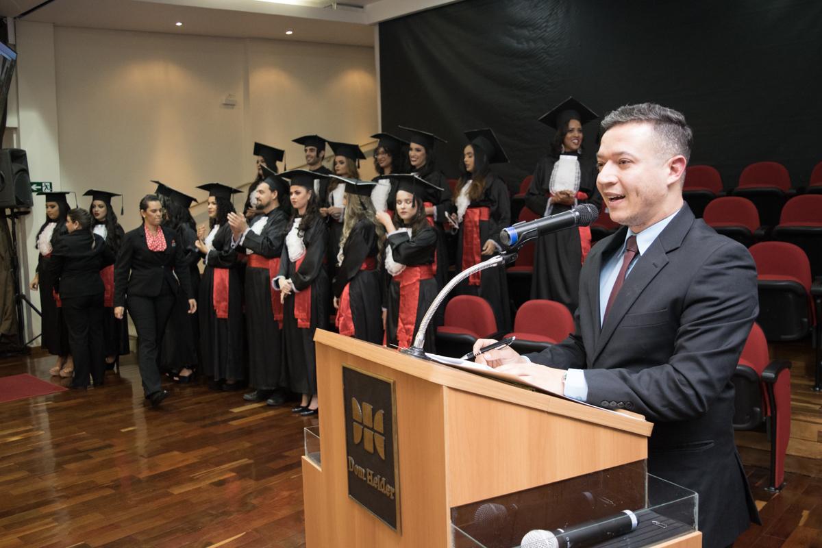 Mestre de cerimônias, professor Gilmar Pereira, conduz a chamada dos formandos.