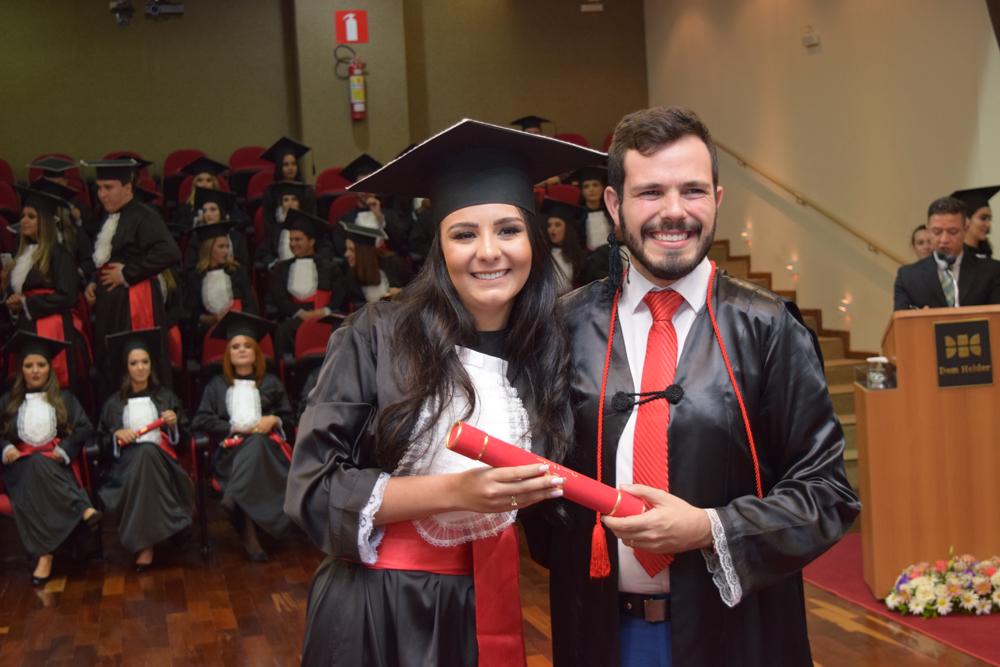O patrono da turma, Thiago Loures, entrega o diploma para a bacharela