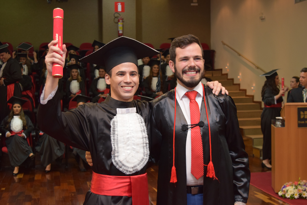 O patrono da turma, Thiago Loures, entrega o diploma para o bacharel
