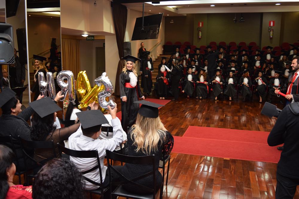 Familiares e amigos de formandos fazem homenagens durante a colação de grau.
