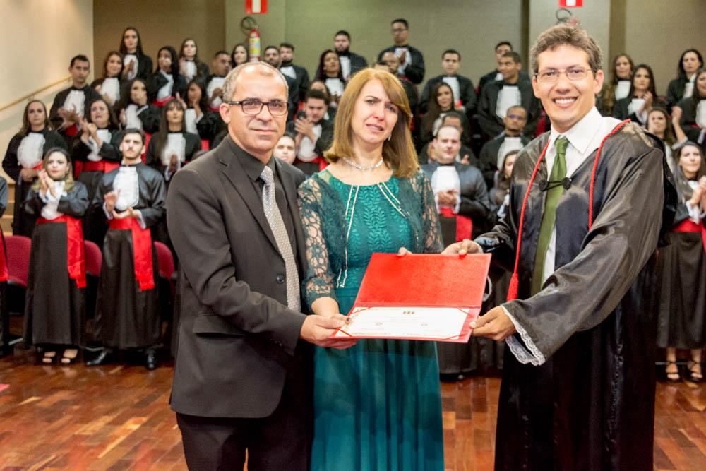 O paraninfo da turma, o professor Pedro Maia faz uma entrega simbólica do certificado aos pais de Delano Ramão Paz.