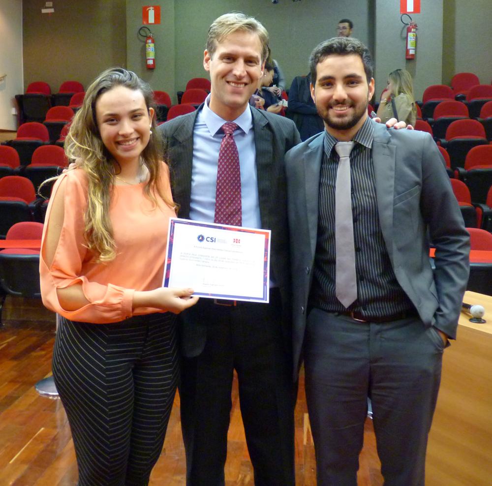 A dupla que ficou em segundo lugar, Izabelle Lauar Shirmer e Paulo Henrique Diniz Pinheiro Machado, recebem o certificado de um dos organizadores da competição, Renato Campos Andrade.