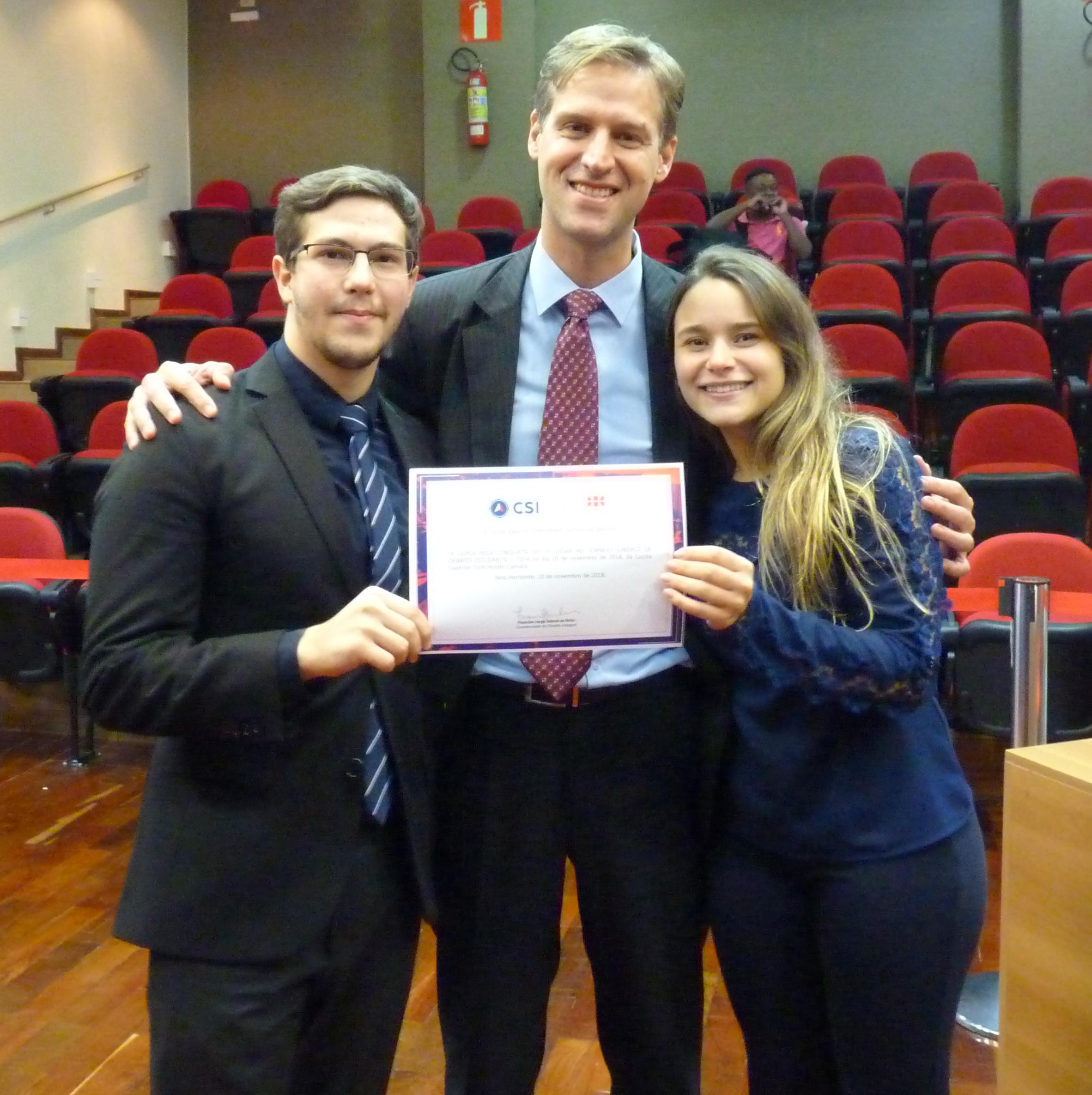 Julia Porto de Miranda e Daniel Boczar Leão, vencedores da 2ª edição do TJD-e recebem o certificado de um dos organizadores da competição, Renato Campos Andrade.