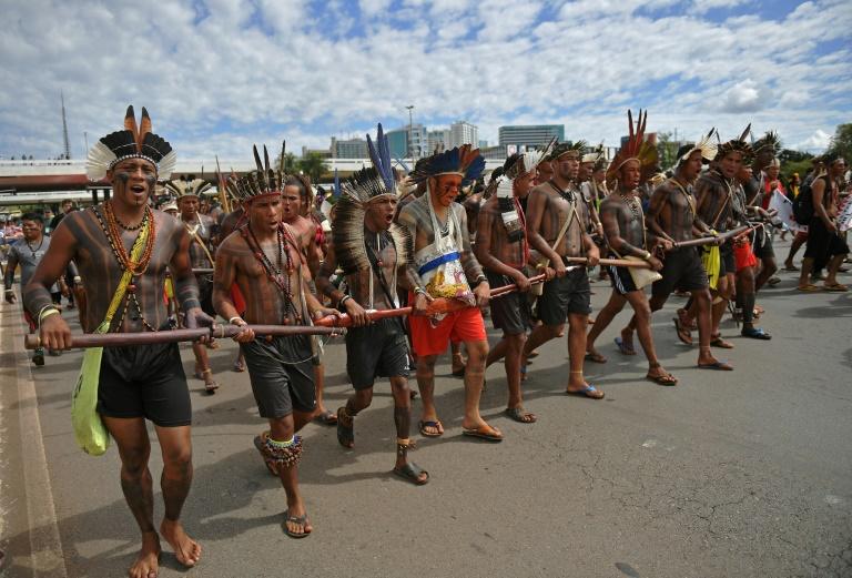 Indígenas caminham na direção de um edifício do governo durante protesto em Brasília