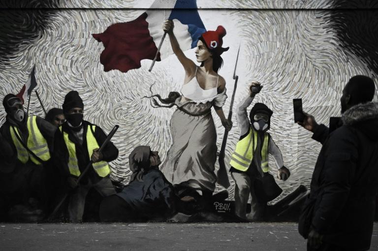 Homem fotografa em 8 de janeiro de 2018, em Paris, um mural do artista de rua PBOY, que recria o quadro de Delacroix, 'A liberdade guiando o povo', mas com os coletes amarelos no lugar dos revolucionários de 1830