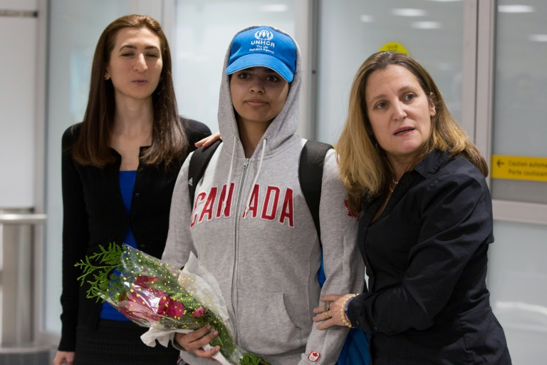 A ministra das Relações Exteriores do Canadá, Chrystia Freeland (D), recebe a saudita Rahaf Mohamed al Qunun (C), em 12 de janeiro de 2019 no aeroporto de Toronto.