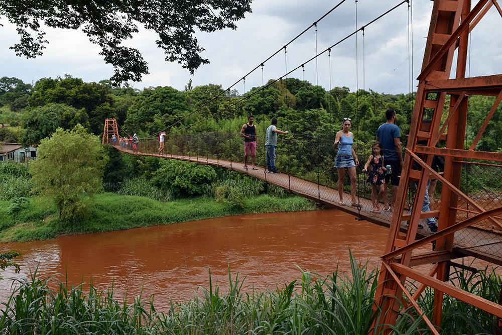 Pessoas observam o rio Paraopeba nas proximidades do município de Mário Campos.