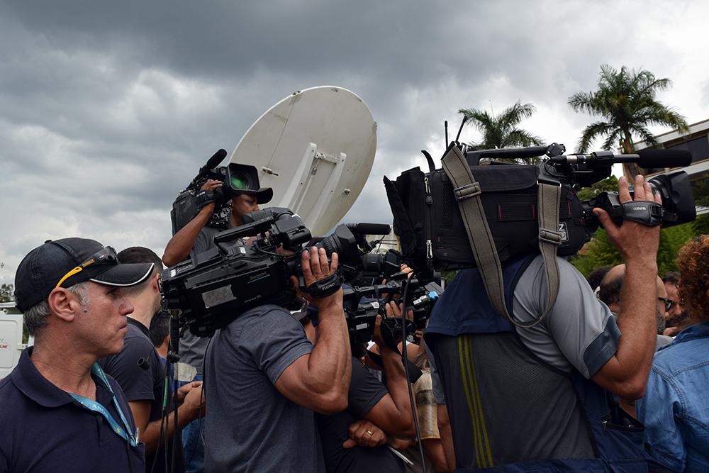 Em frente ao gabinete de crise da tragédia, estruturado na Faculdade Asa, repórteres de diferentes veículos disputavam espaço e informações.
