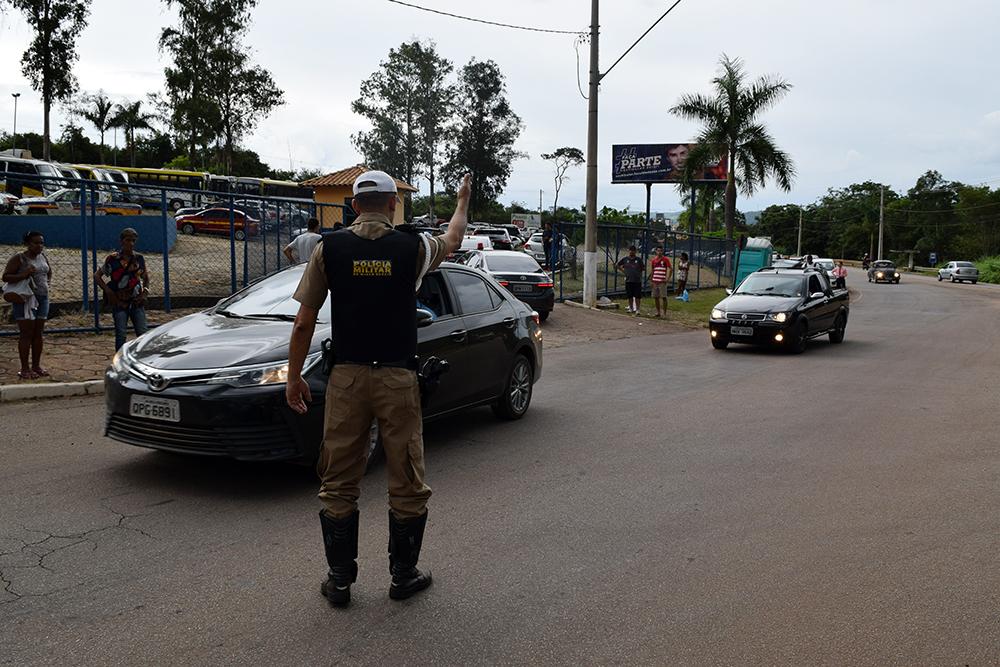 Policial orienta a movimentação de veículos em frente ao gabinete de crise.