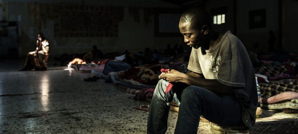 Um migrante senta-se em um ponto de luz entrando por uma das duas únicas janelas em um centro de detenção, localizado na Líbia, em 1º de fevereiro de 2017. Na época da visita do UNICEF, 160 homens estavam detidos no local.