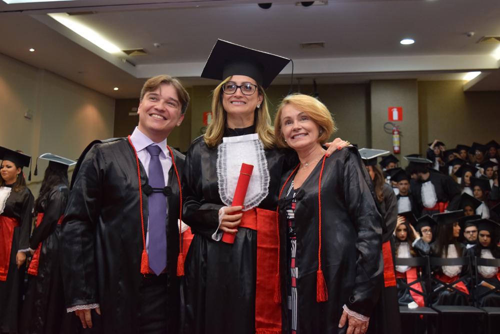 Aluna comemora sua formatura ao lado dos professores Fernando Tolentino e Lígia Maria Veloso