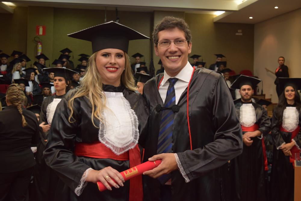O professor Pedro Eliezer entrega diploma a aluna