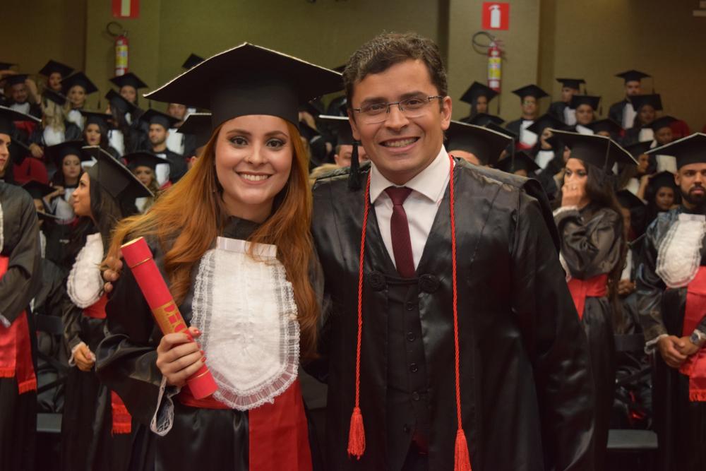 O professor Carlos Amaral entrega diploma a aluna