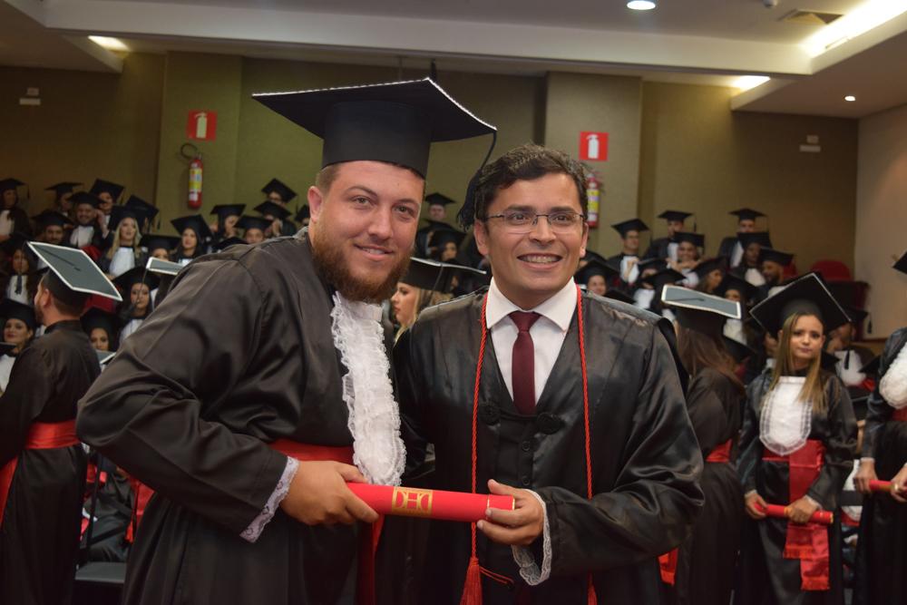 O professor Carlos Amaral entrega diploma a aluno