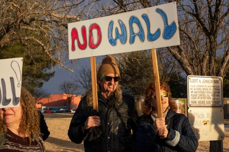 Pessoas exibem cartazes de protesto contra a declaração de emergência nacional pelo presidente Donald Trump em Las Cruzes, Novo México.