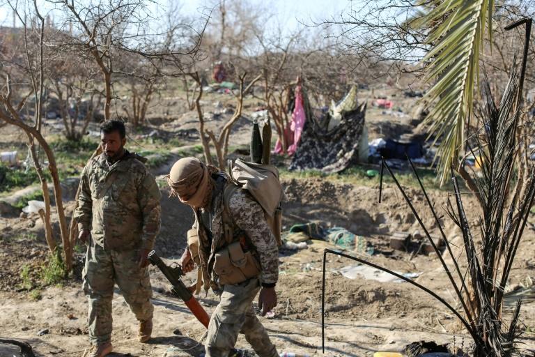 Combatentes das Forças Democráticas Sírias revistam acampamento provisório de membros do EI nos arredores de Baghuz, em 9 de março de 2019