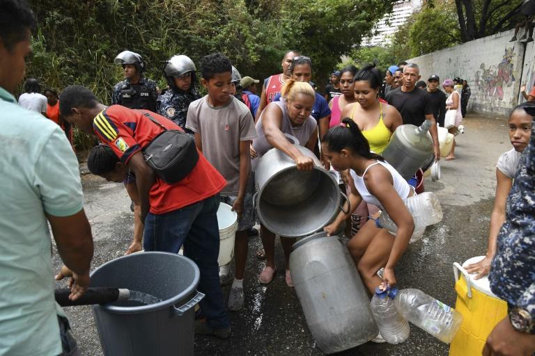 Membros da Polícia Bolivariana Nacional ajudam a organizar a distribuição de água potável para moradores em Caracas, em 11 de março de 2019