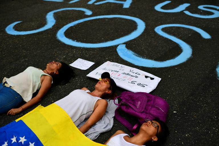 Simpatizantes do líder opositor Juan Guaidó deitam na rua junto a um pedido de SOS, durante uma manifestação em Caracas, no dia 12 de março