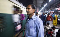 O cego Vinod Kumar Sharma aguarda em uma plataforma na estação Hazrat Nizamuddine, em Nova Délhi, o trem para voltar para casa depois do trabalho (AFP)