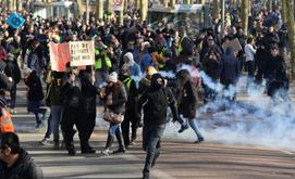 Manifestantes correm para se proteger de bombas de gás lacrimogênio durante protesto contra reforma previdenciária em Bordeaux, França (AFP)