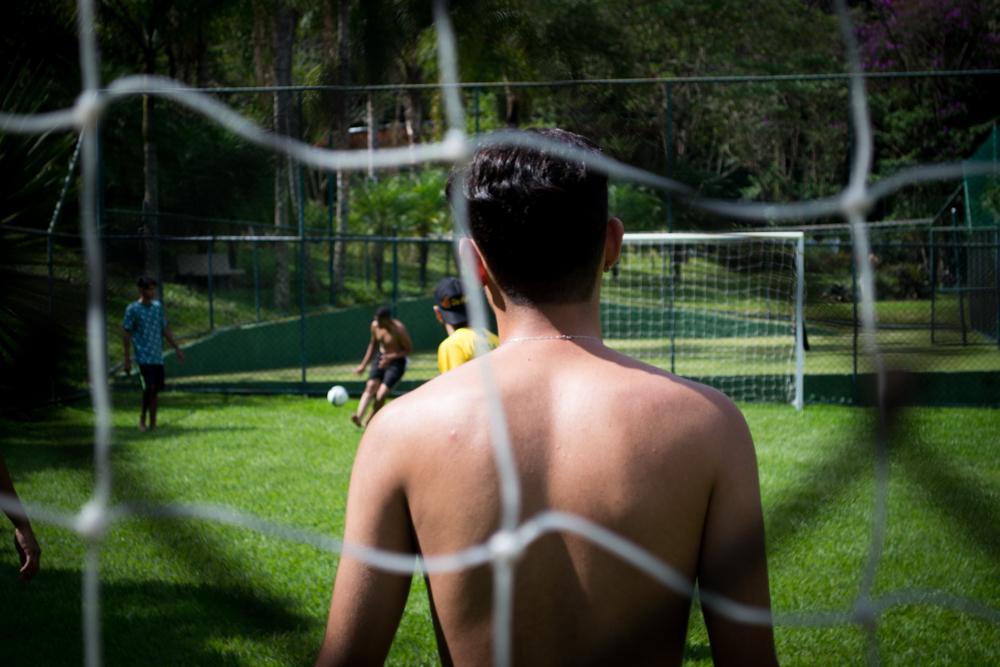 No tempo de lazer, estudantes jogam futebol.