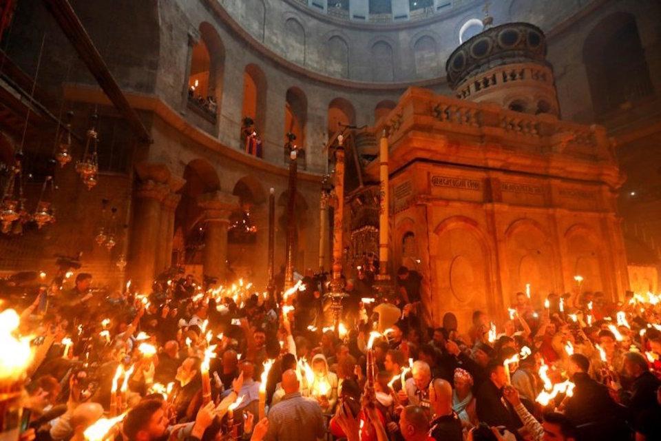Cristãos ortodoxos seguram velas durante o rito do