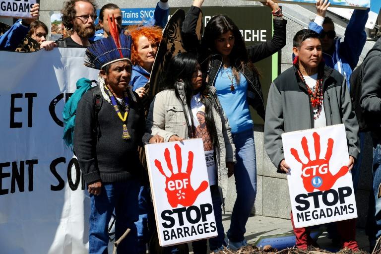 Membros de tribos indígenas da Amazônia se manifestam ao lado de ativistas da 'Extinction Rebellion' (XR) contra grandes hidrelétricas em Puteaux, noroeste de Paris
