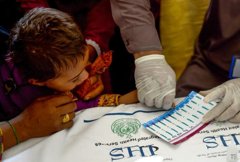 Uma criança é submetida a um exame de HIV, na localidade paquistanesa de Rato Dero