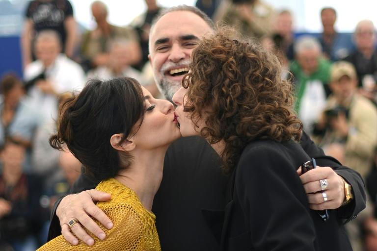 Julia Stockler (esquerda) e Carol Duarte se beiam em frente ao diretor Karim Ainouz, no Festival de Cannes, em 20 de maio de 2019