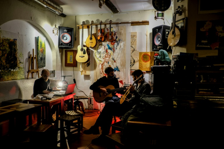 Dois homens tocam violão no Tejo Bar, local frequentado por artistas no Bairro Alfama, em Lisboa