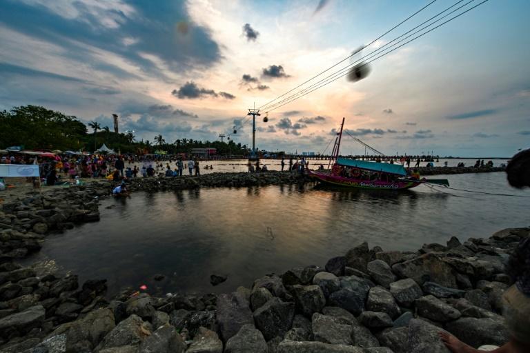 Indonésios aproveitam o pôr do sol na Baía de Jacarta em 7 de junho de 2019, um dia antes do Dia Mundial do Oceano.