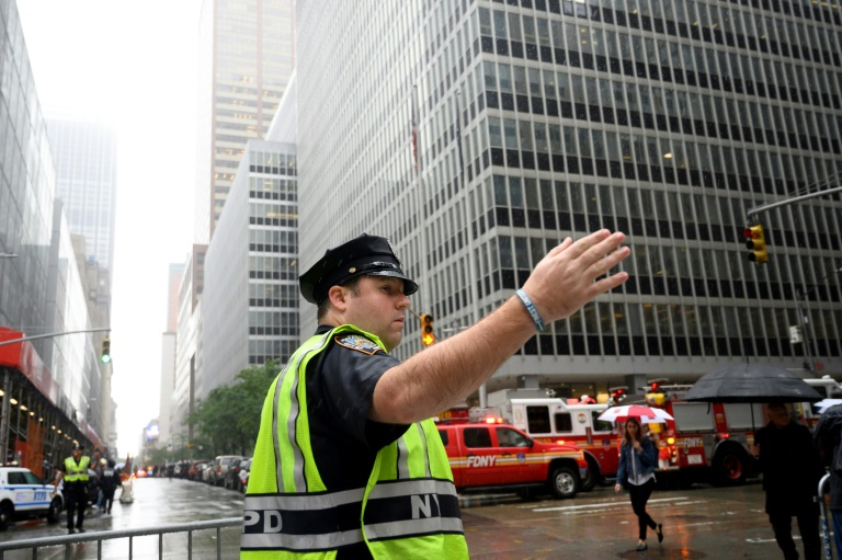 Um policial gesticula perto de caminhões de bombeiros depois que um helicóptero caiu no topo de um prédio no centro de Manhattan, em 10 de junho de 2019.