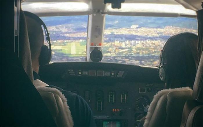 Casal divide o comando de um avião.