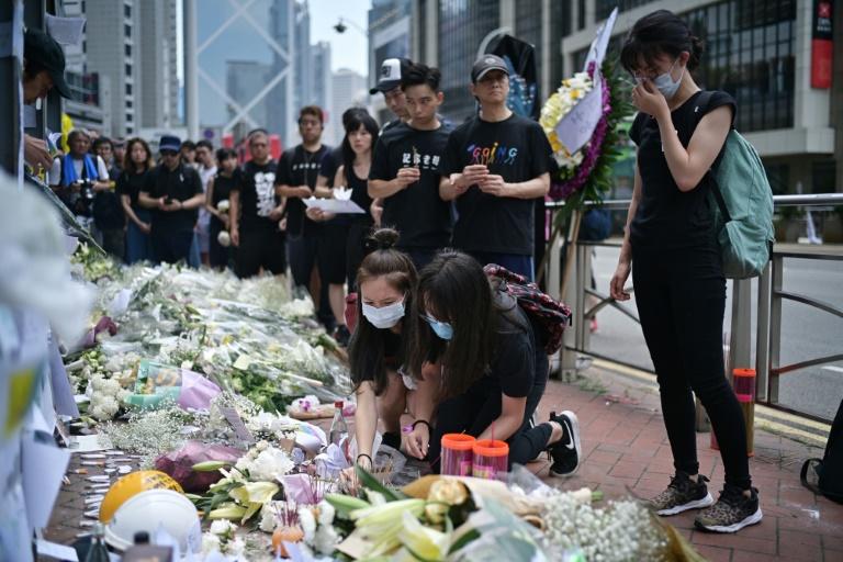Flores e orações no local onde ativista morreu no sábado em Hong Kong.